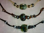 "Rich as Roman mosaics under clear water are these chunky, artisan glass beads.  Together with the kick of hardware ""beads,"" strung on 16""-17"" of the softest suede, and closed with hand-forged sterling silver hook-n-eye clasps, these look great inside the open neck of a button-down shirt.  $47 ea."